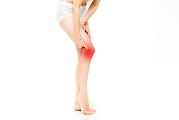 Gelenkschmerzen, weibliche person mit gestrecktem bein