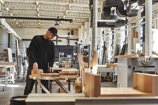 Gelernter tischler in schwarzer uniform, der in seiner holzwerkstatt ein stück holz schneidet