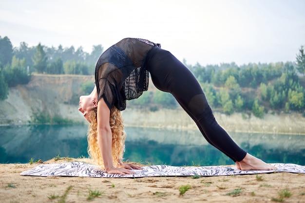 Gelockte frau der attraktiven rothaarigen oder vorbildliches übendes yoga draußen