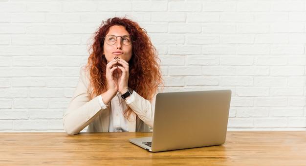 Gelockte frau der jungen rothaarigen, die mit ihrem laptop im verstand bildet plan, eine idee gründend arbeitet.