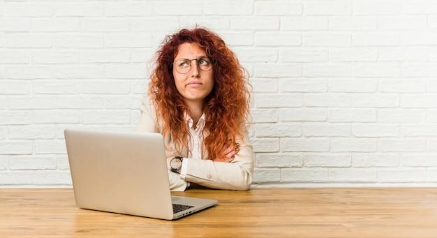 Gelockte frau der jungen rothaarigen, die mit ihrem laptop unglücklich in camera schauen mit sarkastischem ausdruck arbeitet.