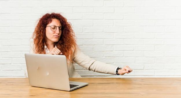 Gelockte frau der jungen rothaarigen, die mit ihrem laptoptanzen arbeitet und spaß hat.