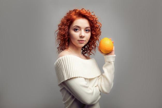 Gelockte frau der schönen rothaarigen, die orange isst