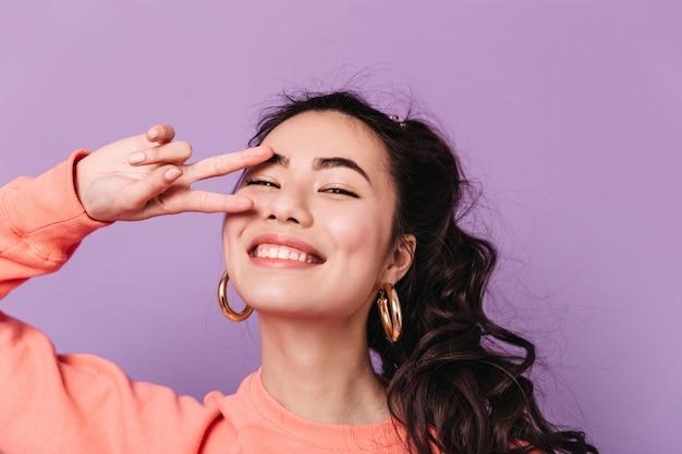 Gelockte japanische frau, die friedenszeichen zeigt. atemberaubendes asiatisches weibliches modell in den ohrringen, die über kamera lachen.