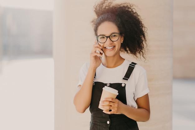 Gelockte jugendliche trägt transparente gläser, spricht am handy, hat die kaffeepause und trägt das weiße t-shirt