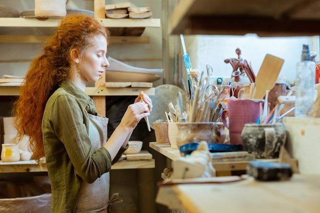 Gelockter frauenhandel. fokussiertes langhaariges ingwermädchen, das den zustand ihrer werkzeuge überprüft, während sie in der nähe der arbeitsfläche bleibt