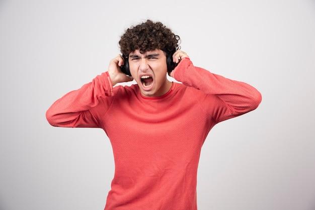 Gelockter junger mann mit kopfhörern, der ein lied mit lauter lautstärke hört.