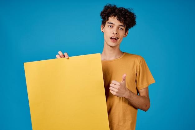 Gelockter kerl mit gelbem mockupplakatblauhintergrund. foto in hoher qualität