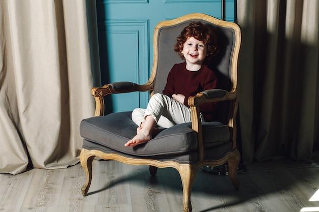 Gelockter kleiner junge in der burgunder-strickjacke und in weißen hosen, die in einem lehnsessel sitzen und an der kamera lächeln