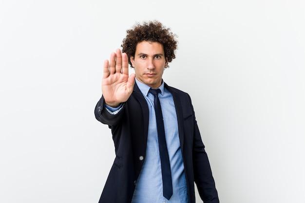 Gelockter mann des jungen geschäfts gegen den weißen hintergrund, der mit der ausgestreckten hand zeigt das stoppschild, sie verhindernd steht.
