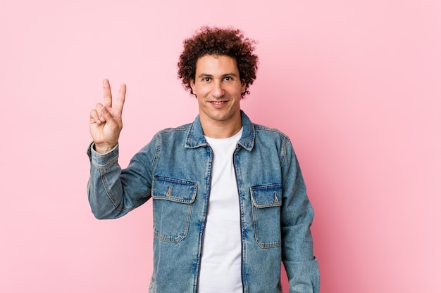 Gelockter reifer mann, der eine denimjacke gegen die rosa wand zeigt siegeszeichen und breit lächelt trägt.