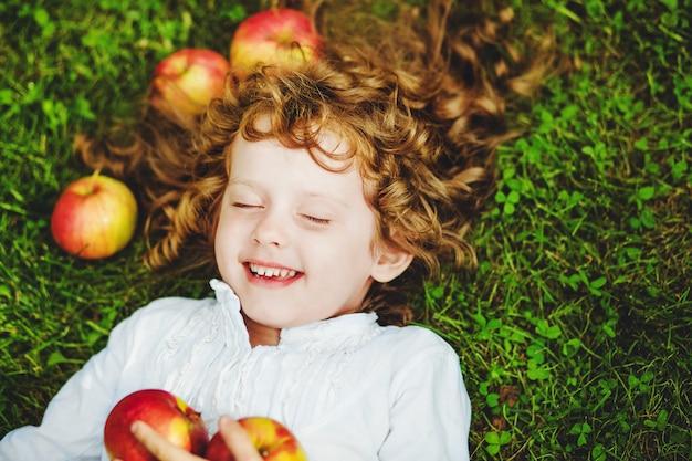 Gelocktes mädchen liegt auf dem gras mit apfel und dem lächeln.