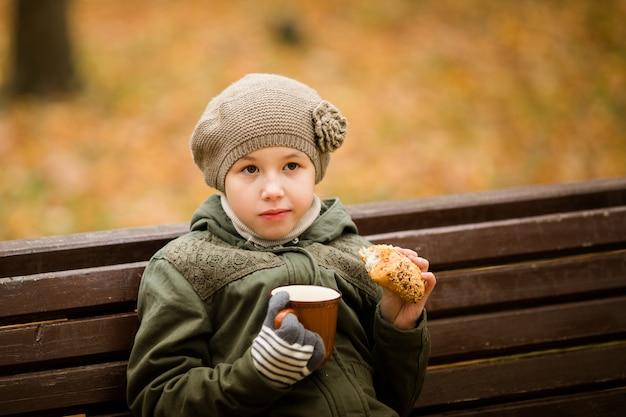 Gelocktes schulmädchen in den gläsern und im hellen mantel, die auf der niederlassung im herbstpark sitzen und geschmackvollen kuchen essen und tee auf dem sonnenuntergang trinken