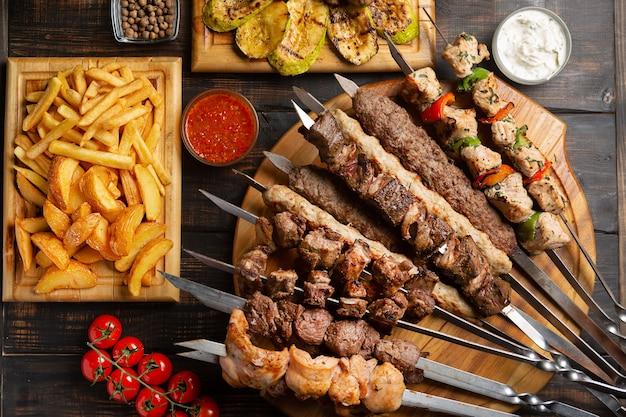 Gemachtes gericht aus spießen, gegrilltem hühnchen, rind, schweinefleisch mit grill und tzatziki-sauce, serviert mit pommes frites im dunkeln.