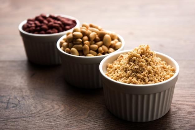 Gemahlene erdnüsse oder mungfali-pulver mit ganzen und gerösteten erdnüssen. serviert in einer schüssel über stimmungsvollem hintergrund. selektiver fokus