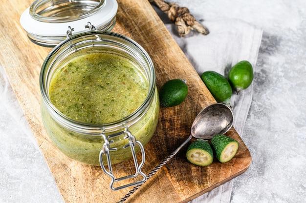 Gemahlene grüne feijoa mit zucker auf einem hölzernen schneidebrett in einem glas. grauer hintergrund. draufsicht.