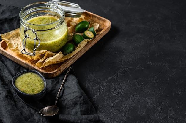 Gemahlene grüne feijoa mit zucker auf einem hölzernen schneidebrett in einem glas. schwarzer hintergrund. draufsicht