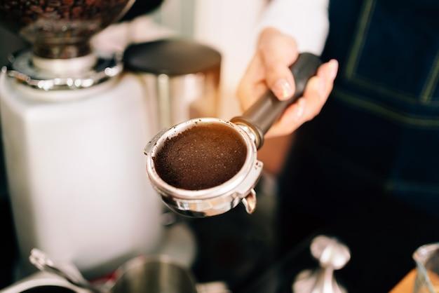 Gemahlene kaffeebohne der nahaufnahme im metallfilter mit griff, der durch frauenhand hält. kaffeezubereitungsklassen für unternehmer, um kleine unternehmen zu gründen.