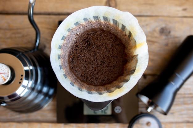 Gemahlene kaffeebohnen in einem trichter. kaffeebrühritual. kaffee zu hause machen. gefilterter kaffee oder überlauf ist eine methode, bei der wasser auf gerösteten kaffee gegossen wird