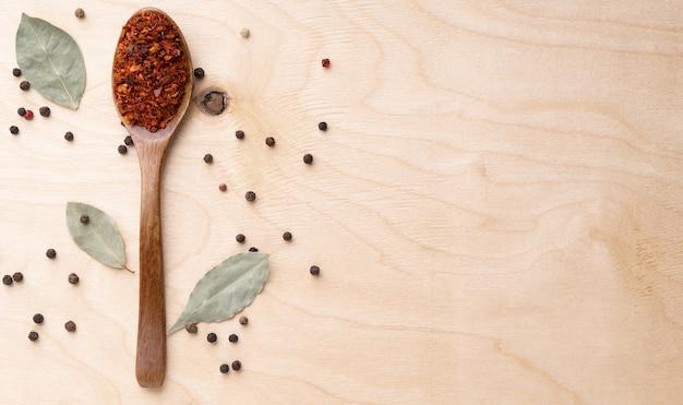 Gemahlener chili im hölzernen löffel auf hölzernem hintergrund.