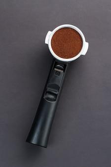 Gemahlener espresso in einem halter auf schwarzem hintergrund