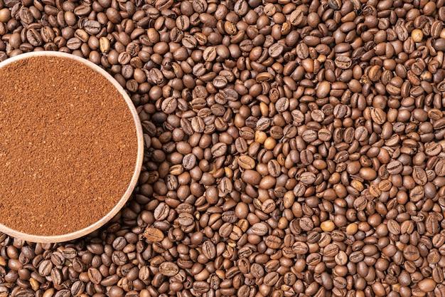 Gemahlener kaffee in holzplatte auf kaffeebohnen hintergrund. ansicht von oben. platz kopieren