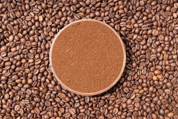 Gemahlener kaffee in holzplatte auf kaffeebohnen hintergrund. ansicht von oben