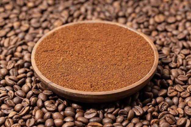 Gemahlener kaffee in holzplatte auf kaffeebohnen hintergrund