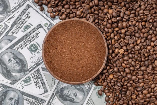 Gemahlener kaffee in holzplatte isoliert auf kaffeebohnen und dollar-banknoten-hintergrund. ansicht von oben