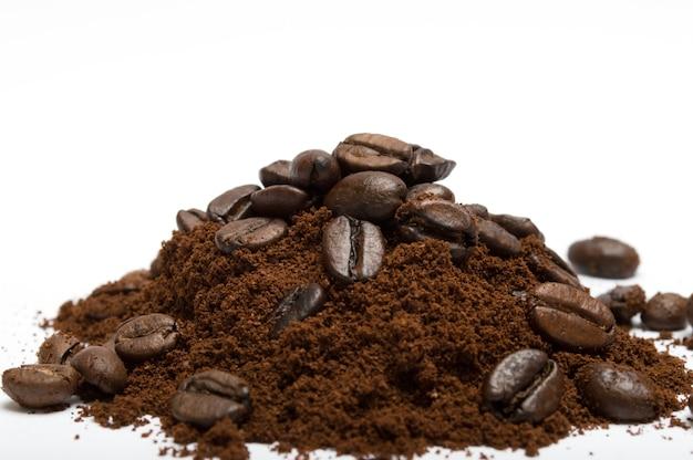 Gemahlener kaffee mit bohnen auf weißem hintergrund