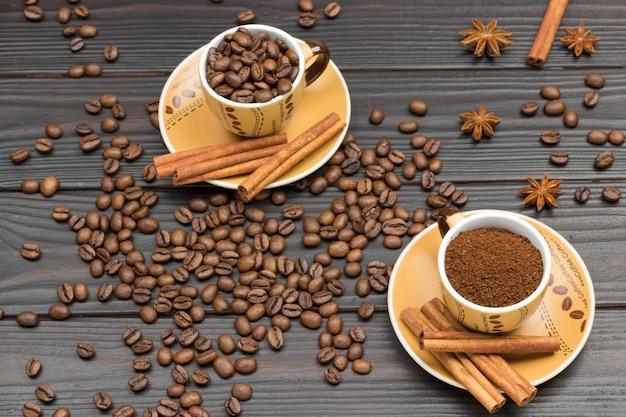Gemahlener kaffee und geröstete kaffeebohnen in tassen. zimtstangen auf untertasse. kaffeebohnen und sternanis auf dem tisch. dunkler holzhintergrund. flach legen