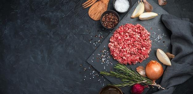 Gemahlenes putenfleisch mit pfeffer, zwiebel und rosmarin auf einem schwarzen betonhintergrund.