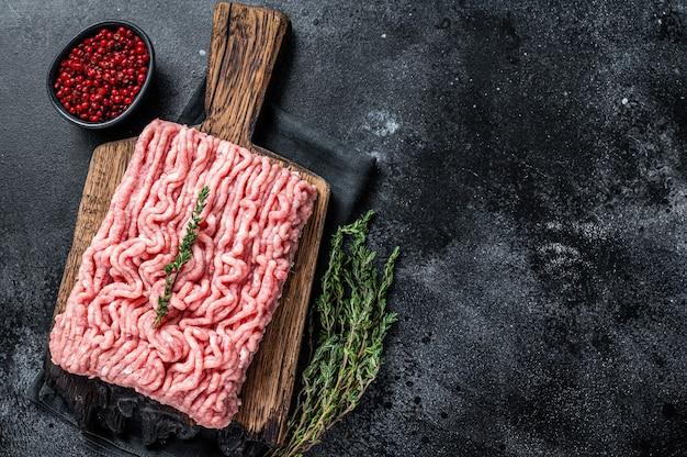 Gemahlenes rohes fleisch von huhn oder pute auf holzbrett. schwarzer tisch. draufsicht.