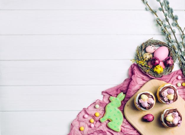 Gemalte eier im natürlichen nest, in den kleinen kuchen und im ingwerbrot auf hellem hölzernem hintergrund