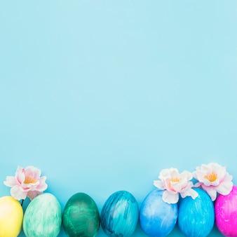 Gemalte eier mit blumen auf blauem hintergrund