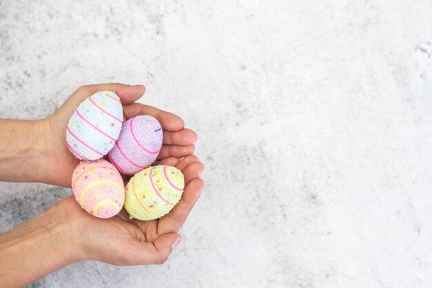 Gemalte gekochte eier in den weiblichen händen nahaufnahme auf einem weiß.