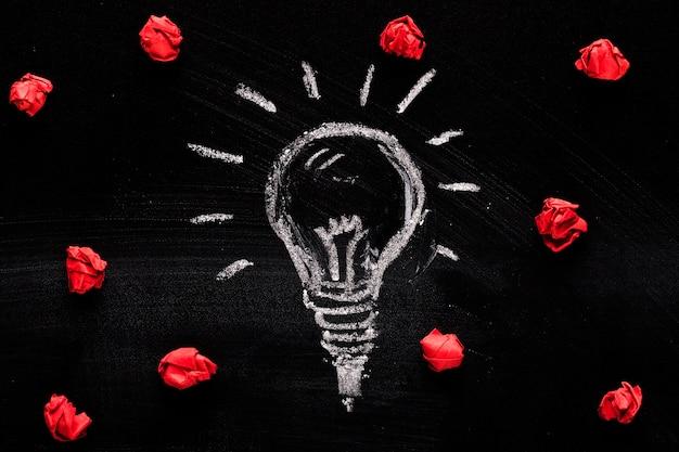 Gemalte glühlampe und zerknittertes papier auf schwarzem hintergrund