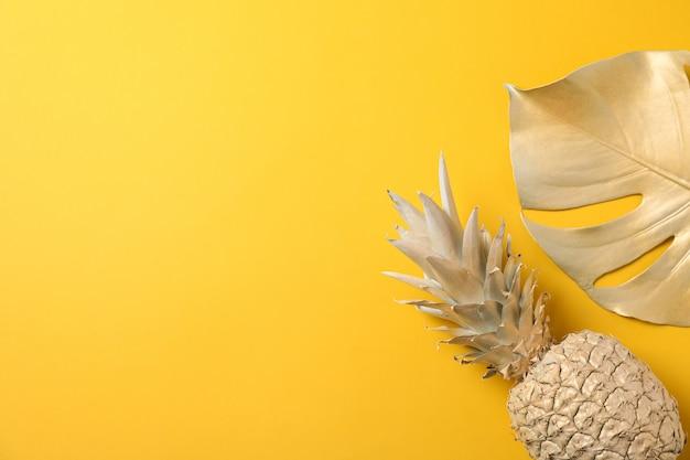 Gemalte goldene ananas und palmblatt auf gelbem hintergrund