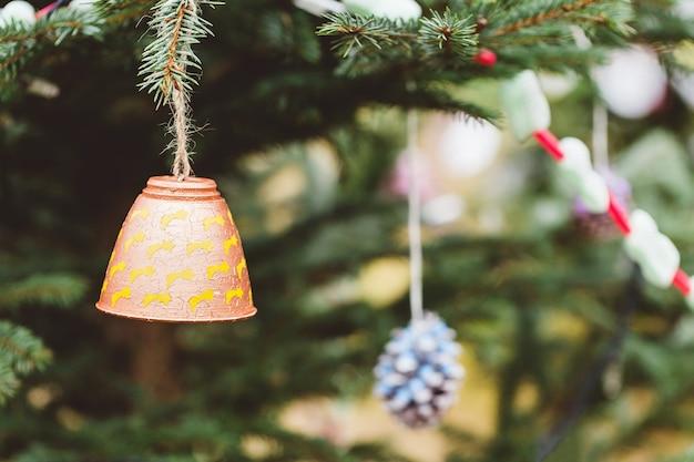 Gemalte handgemachte weihnachtsdekoration auf einem baum im freien, kein schnee. diy ideen für kinder. umwelt-, recycling-, upcycling- und null-abfall-konzept. selektiver fokus, kopierraum