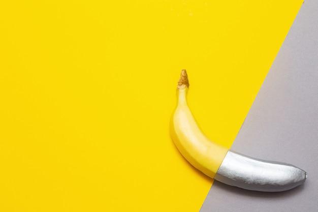 Gemalte silberne banane auf einer gelben und grauen wand