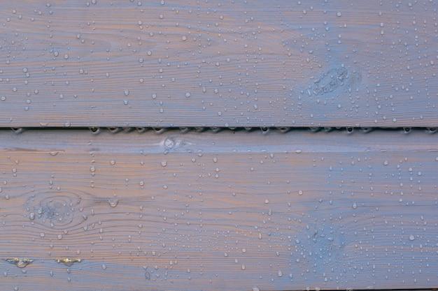 Gemalter holzzaunhintergrund mit regenwassertropfen, nass, viel kontrastholzstruktur, horizontal