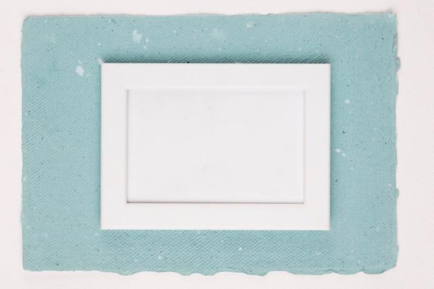 Gemalter weißer rahmen auf strukturiertem papier über weißem hintergrund
