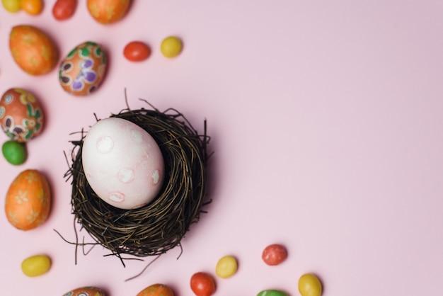 Gemaltes ei für den feiertag des leichten osters in einem nest von zweigen neben süßigkeiten und lebkuchenplätzchen. osterkarte auf einem rosa hintergrund