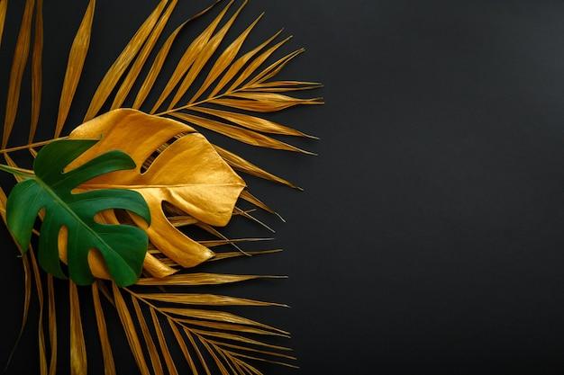 Gemaltes gold verlässt waldmuster auf schwarzem blumenhintergrund der sommernatur. goldenes palmblatt und grüne frische tropische monstera hinterlassen texturrahmen auf dunkelschwarzem hintergrund mit kopierraum.
