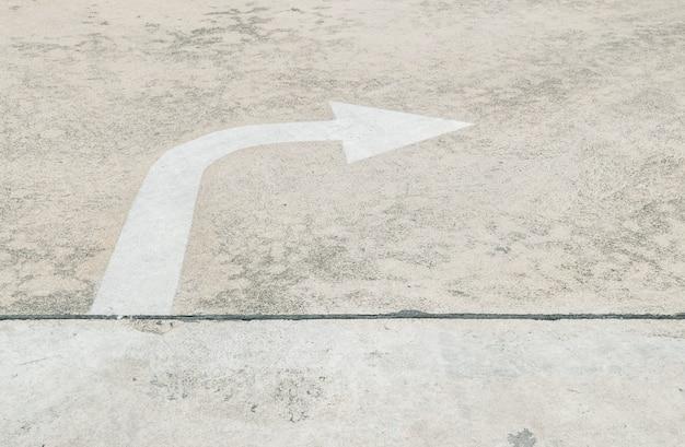 Gemaltes pfeilzeichen der nahaufnahme weiß herein rechte seite auf zementstraßenboden maserte hintergrund