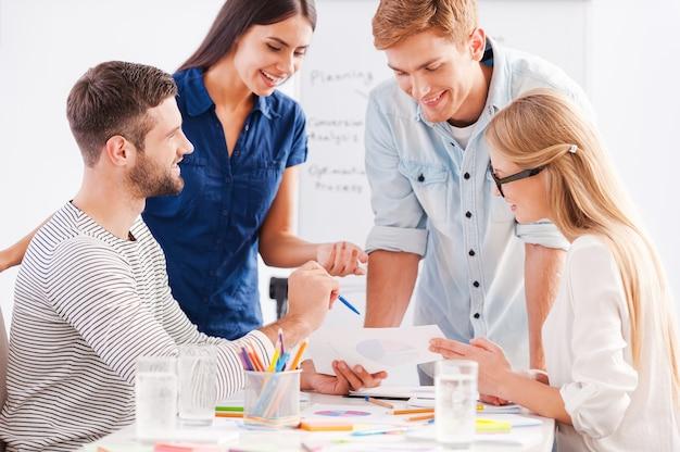 Gemeinsam am projekt arbeiten. vier fröhliche geschäftsleute in eleganter freizeitkleidung diskutieren etwas, während sie sich das dokument gemeinsam ansehen