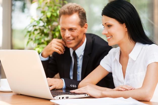 Gemeinsam am projekt arbeiten. zwei geschäftsleute in formeller kleidung, die auf den laptop schauen und lächeln, während sie zusammen im freien sitzen