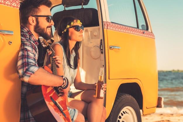 Gemeinsam den sommertag genießen. fröhliches junges paar, das zeit zusammen genießt, während es in seinem retro-minivan mit meer im hintergrund sitzt