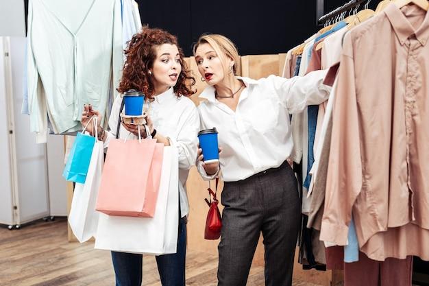 Gemeinsam einkaufen. mutter und tochter wählen beim gemeinsamen einkauf stylische bürohemden aus