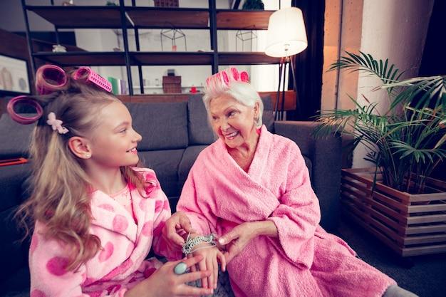 Gemeinsam glücklich fühlen. mädchen und ihre oma mit lockenwicklern fühlen sich am wochenende glücklich zusammen